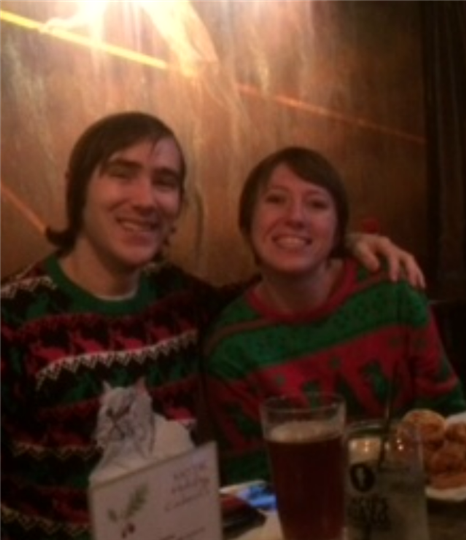 two customers smiling together while wearing ugly christmas sweaters