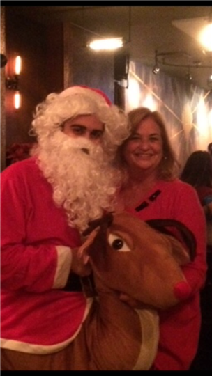 a customer smiling with santa and a reindeer