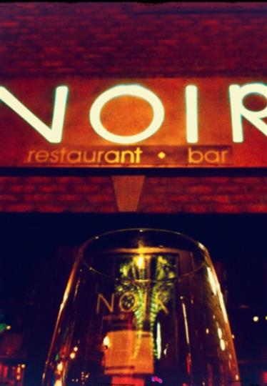 logo of noir with a glass of wine
