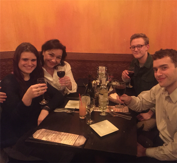 four customers smiling and holding up their glasses of red wine