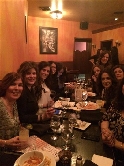 10 women smiling around their table