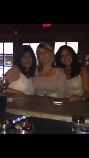three women smiling at the bar