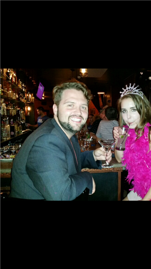 a man posing with a birthday girl who is wearing a tiara and boa