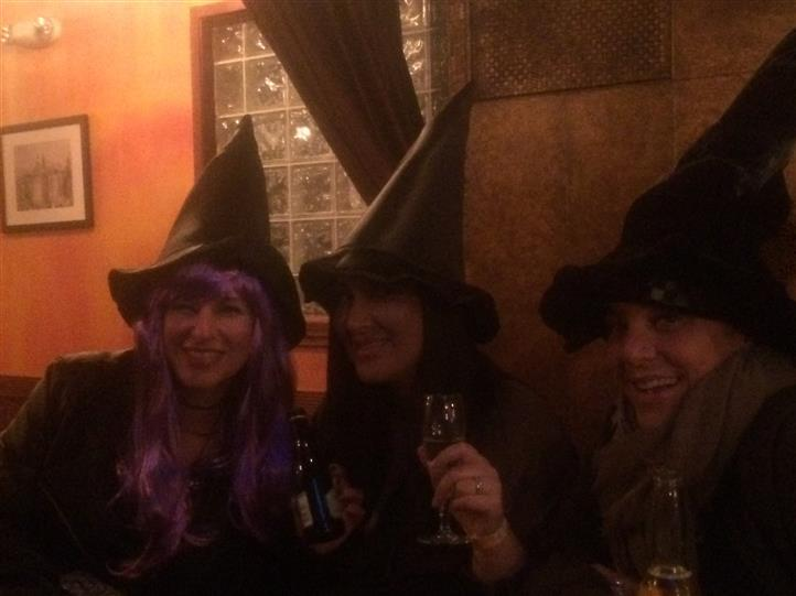 three customers smiling and wearing witch hats while holding glasses of wine