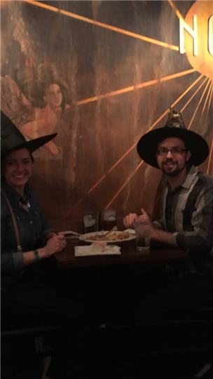 a couple smiling at their table while wearing witch hats