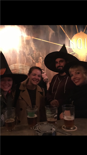 a group of four friends posing together while half of them wear witch hats