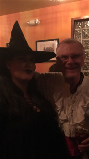 a couple posing together wearing a witch hat