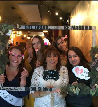 five women posing with bridal shower attire