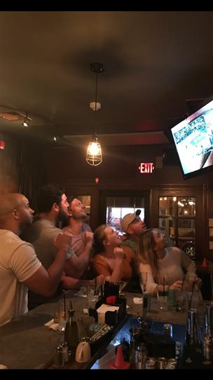 a group of friends watching a game on the tv at the bar