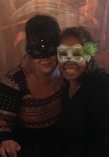 two women smiling while wearing masquerade masks