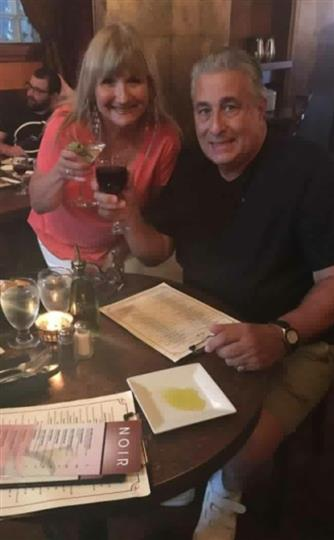a couple smiling with a glass of wine and a martini