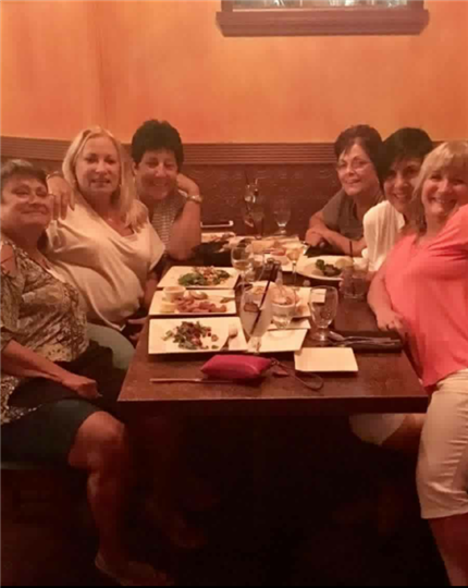 six women smiling at their table and having fun