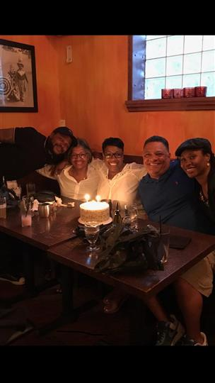 five family members smiling with a lit birthday cake