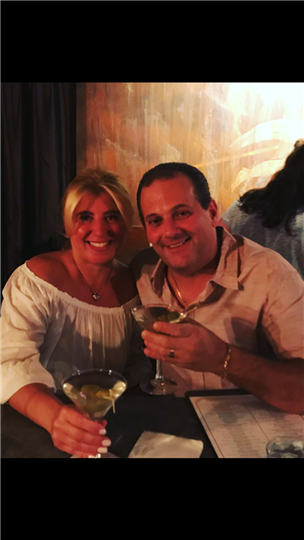 a man and woman smiling and holding their martinis