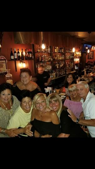 7 customers smiling together at the bar