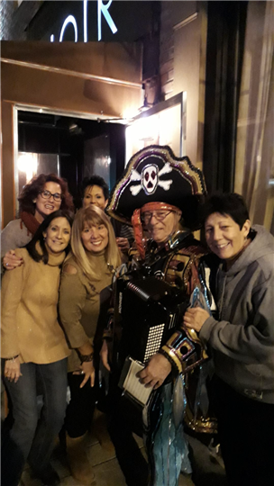 five customers smiling and posing with a man dressed like a pirate