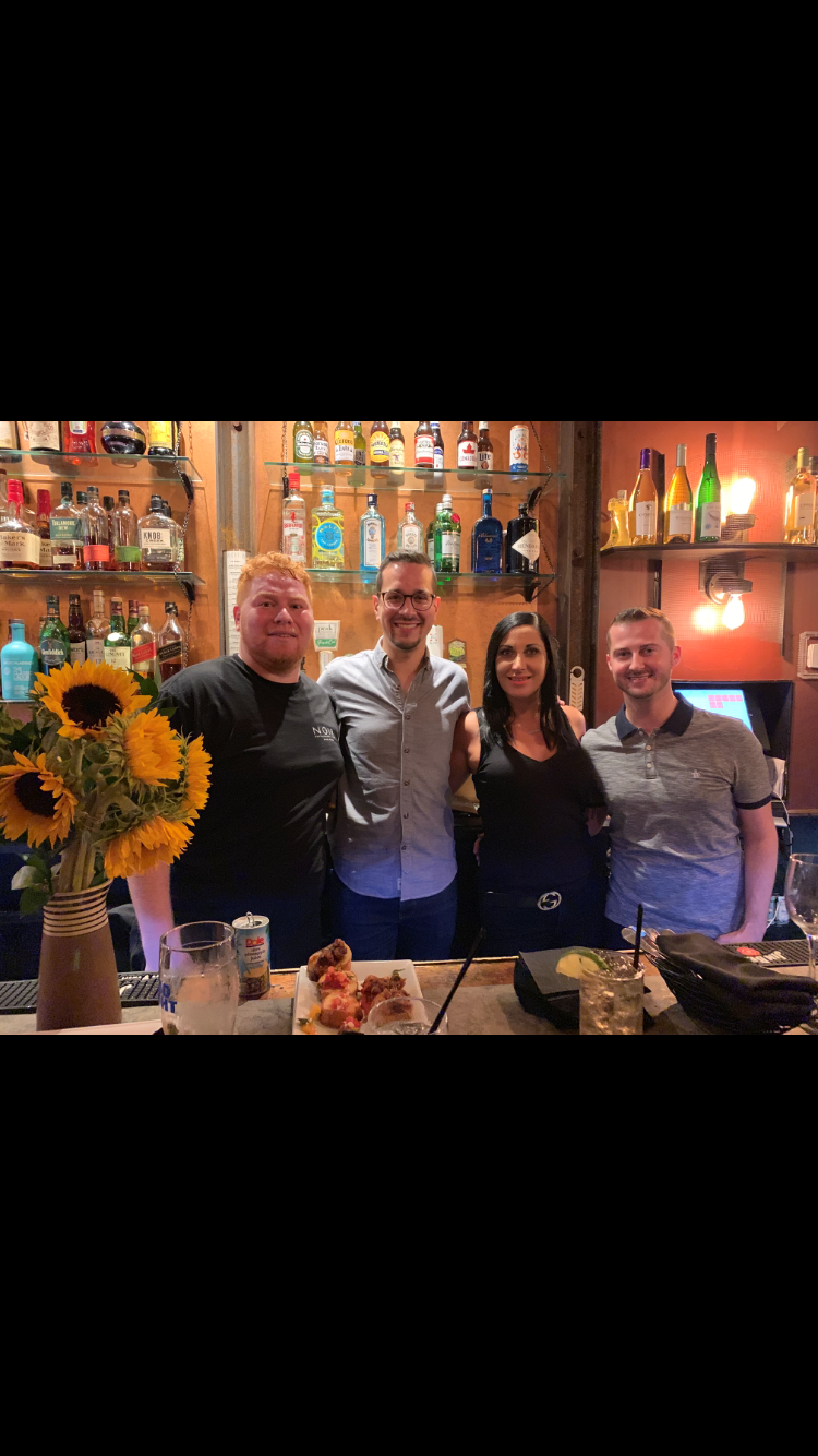 Four staff members smiling and posing behind the bar