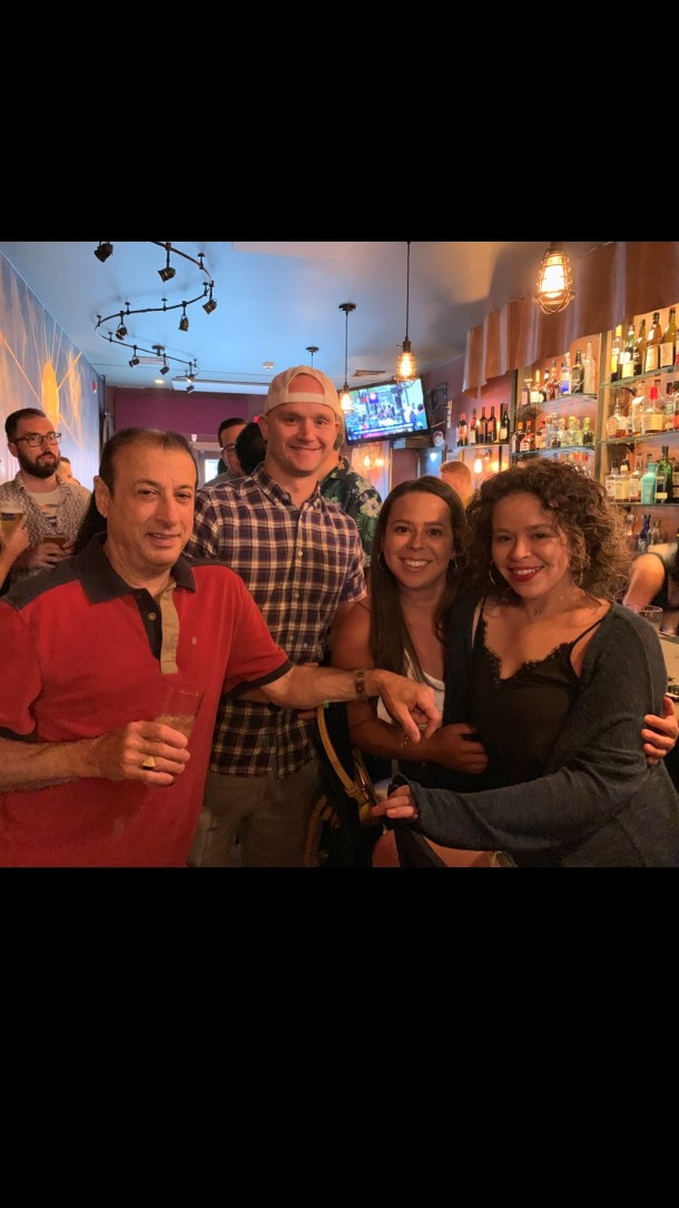 Four guests miling and posing with drinks at the bar