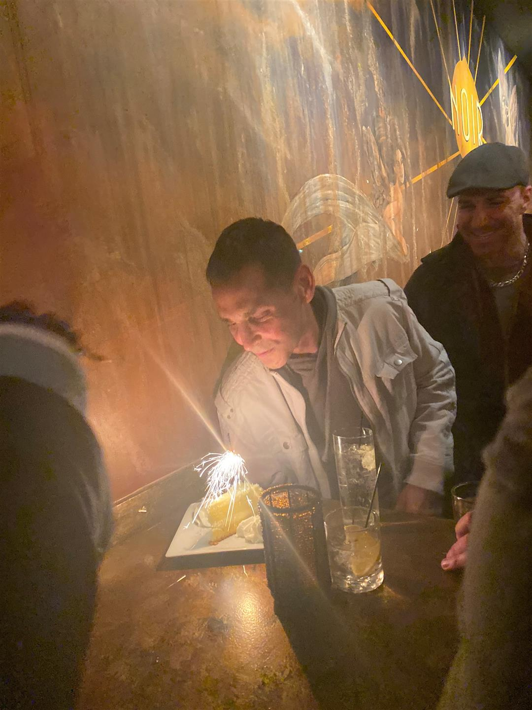 A man blowing out a candle on a piece of cake