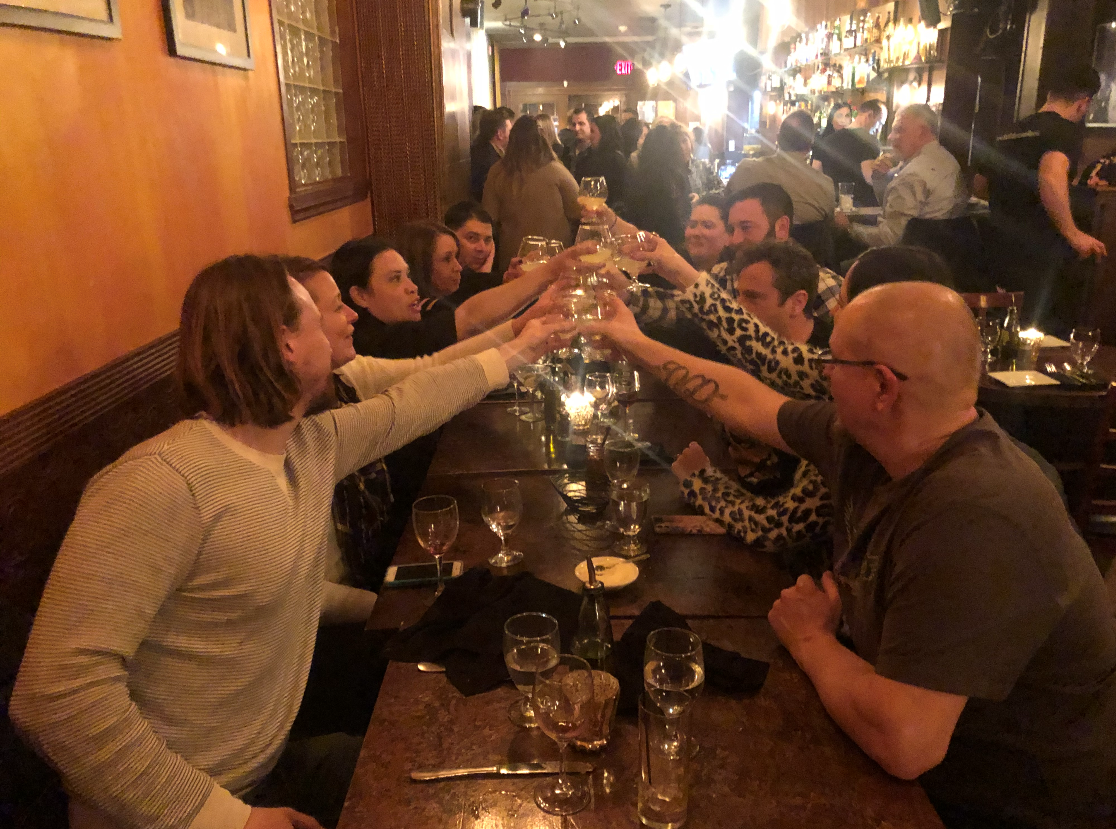 table of customers cheersing their glasses