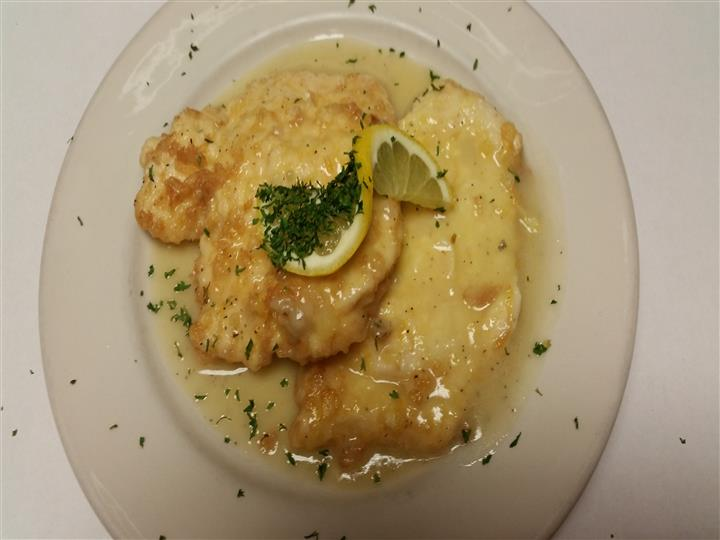 Fish marinated in sauce with a lemon slice