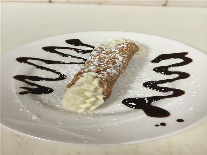Crepe filled with whipped cream with chocolate syrup on the side