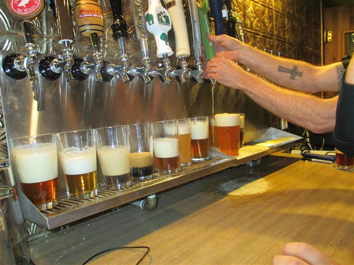 various pints of beer being poured from the tap