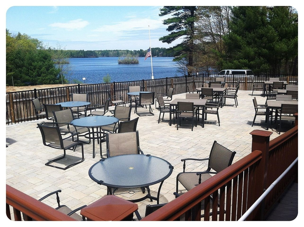 Outside patio area with tables and chairs overlooking a lake