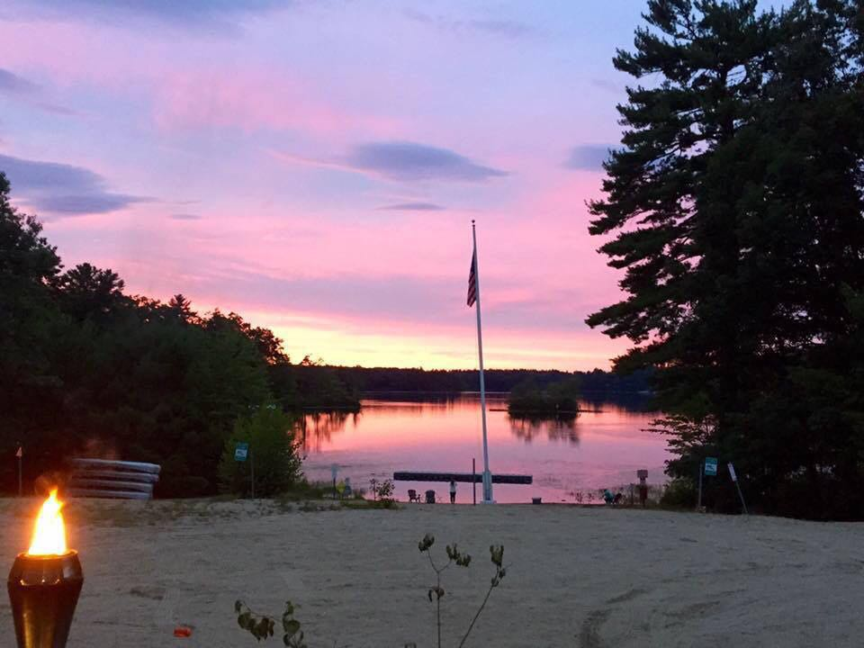 pink sky during sunset reflecting pink onto the lake with view of beach and flag pole