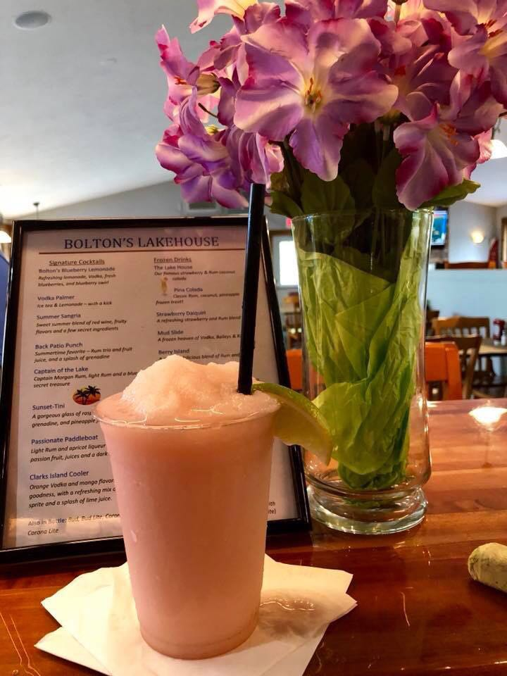 frozen blended pink drink in front of bolton's lake house drink menu