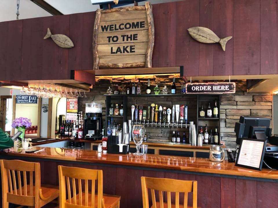 view of indoor bar with wood counters and sign above bar that says 'welcome to the lake'
