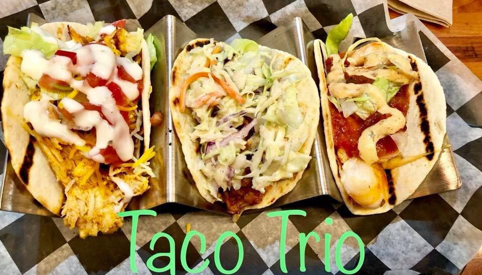taco trio lined up with sauce and slaw