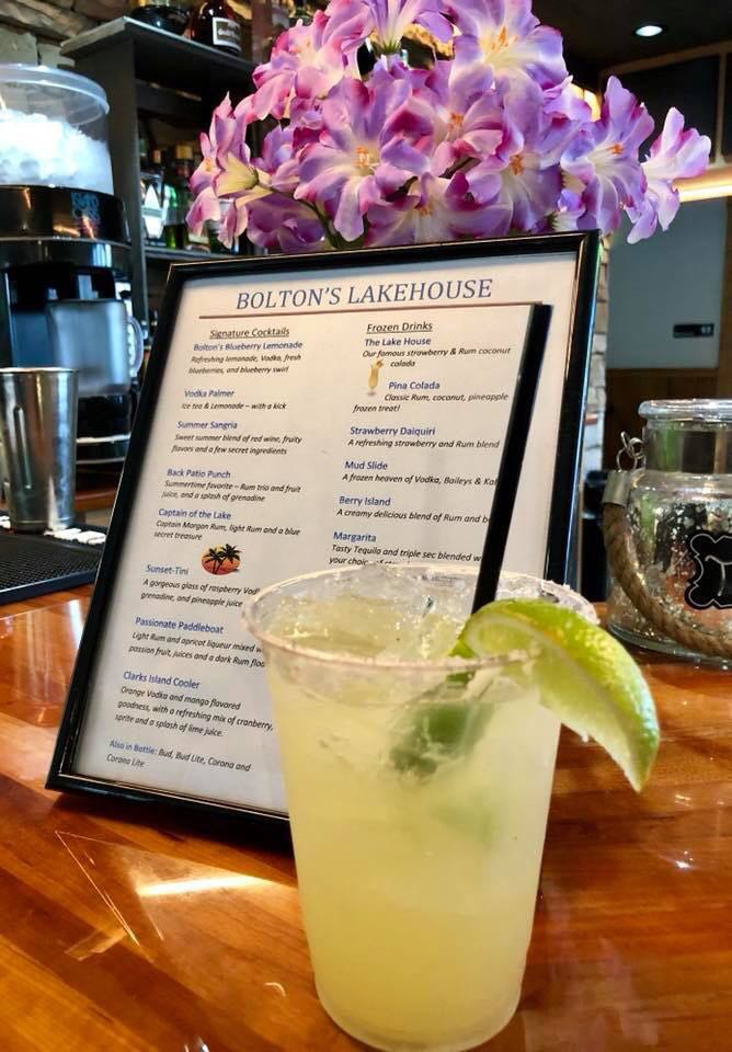 margarita with lime and salted rim placed in front of bolton's lake house drink menu