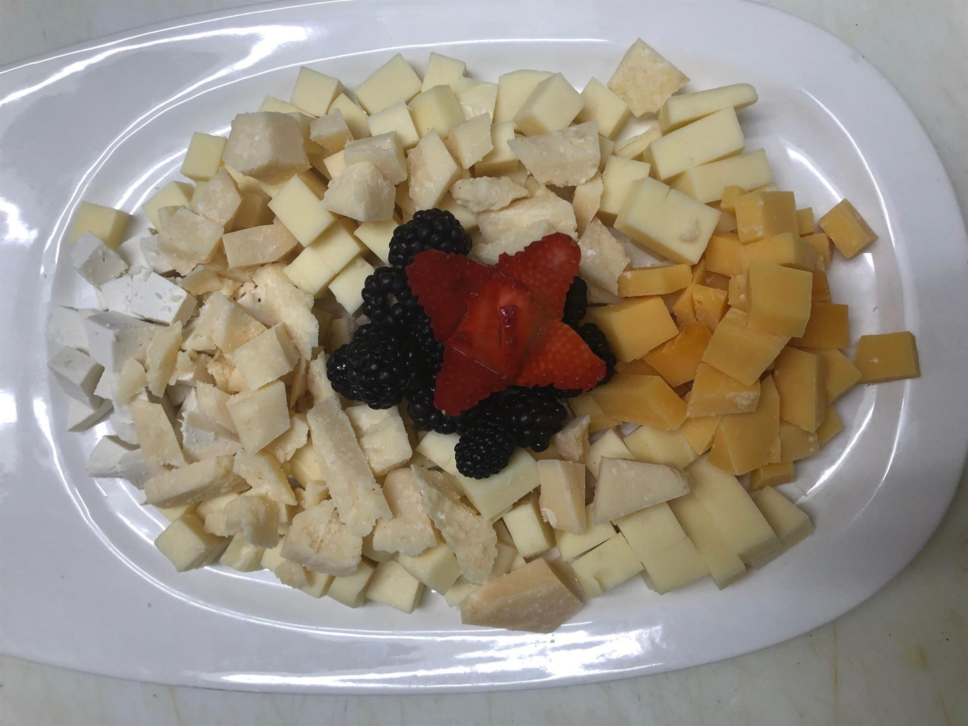 plate of various cheeses with fresh fruit