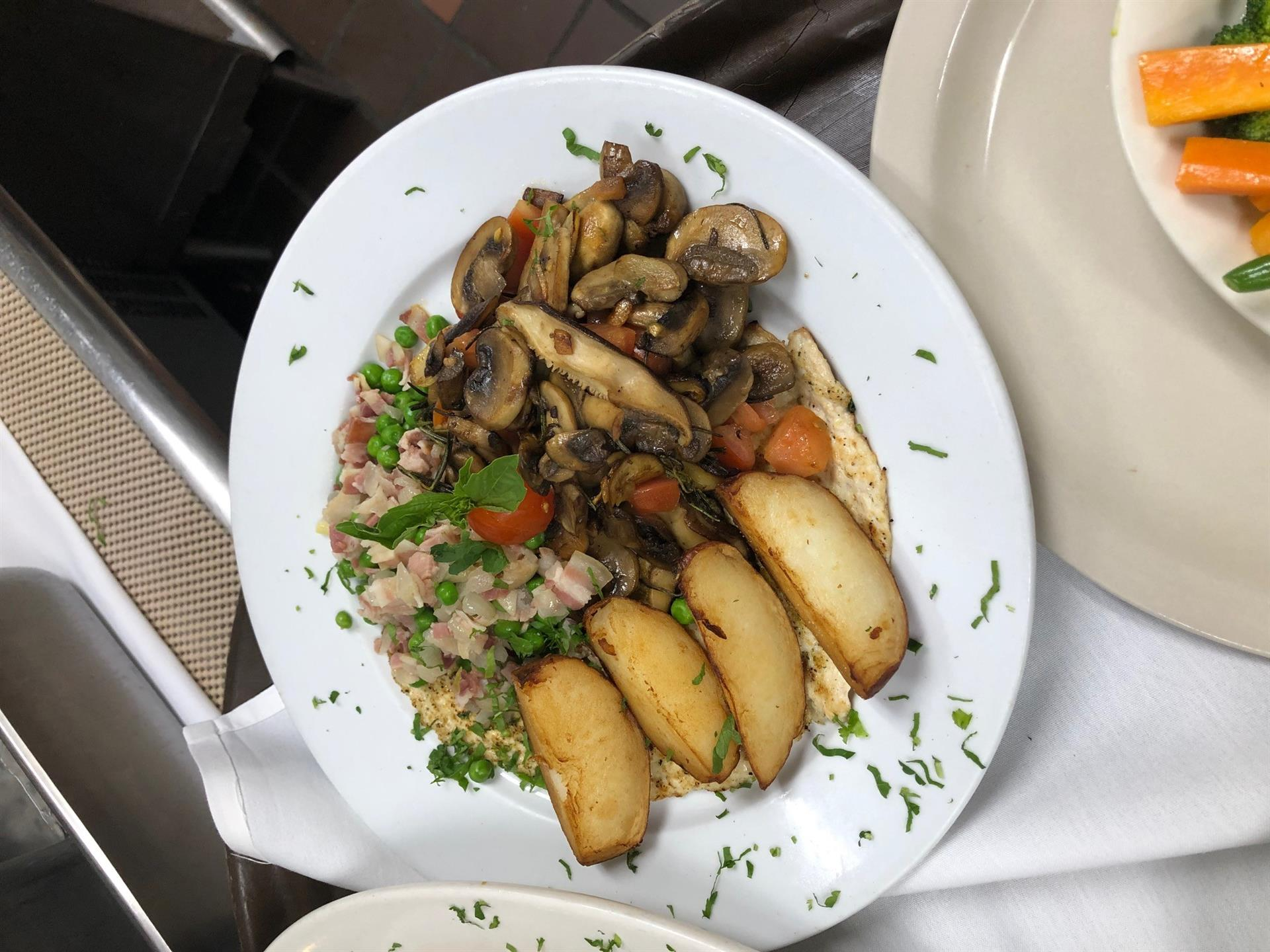 cooked chicken topped with mushrooms and a side of potatoes