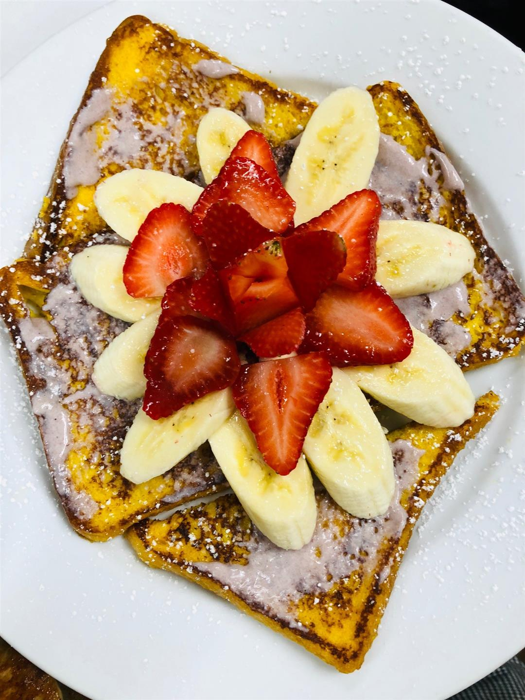 French toast topped with bananas, strawberries and powdered sugar