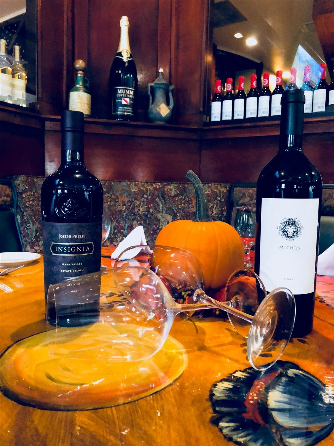 two wine bottles on a table with wine glasses and pumpkin decorations