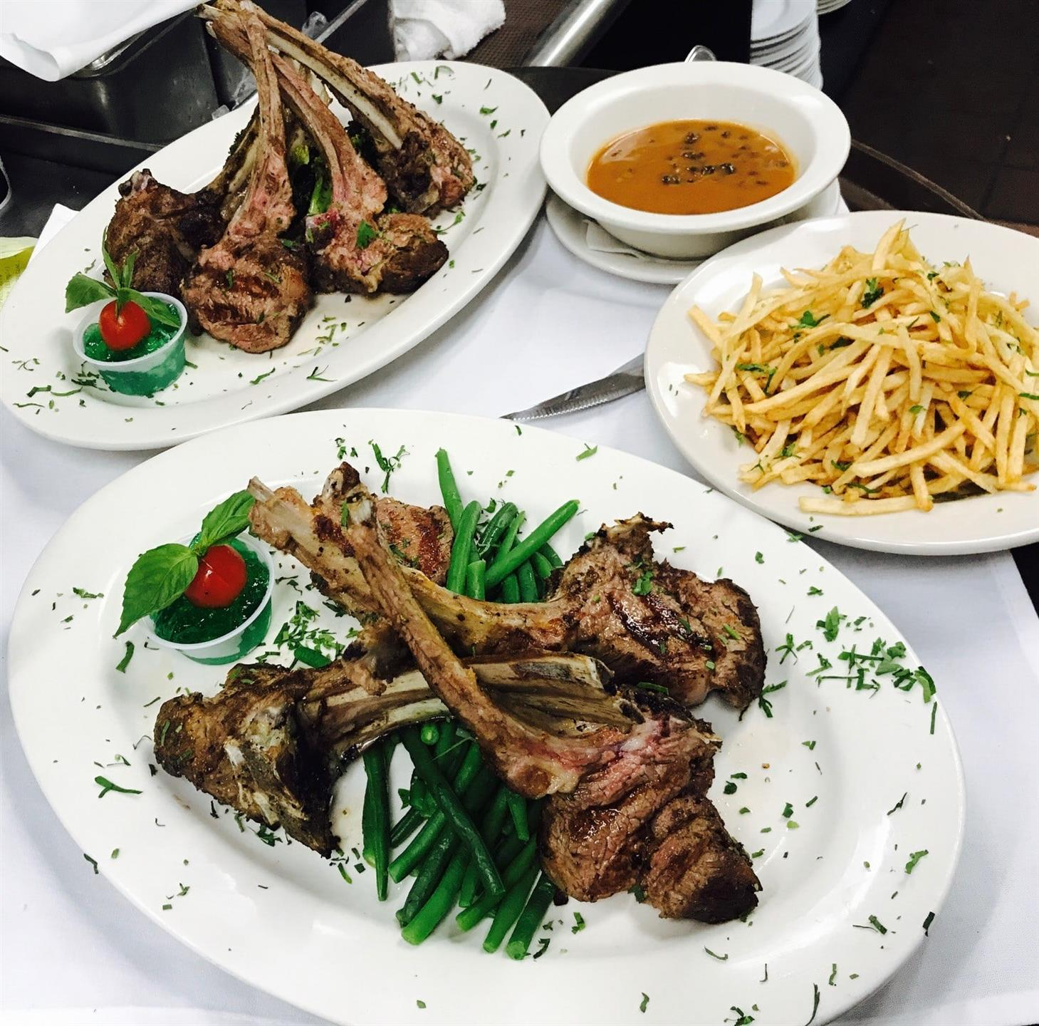 Grilled Lamb Shanks over a bed of green beans topped with sauce and a plate of French Fries