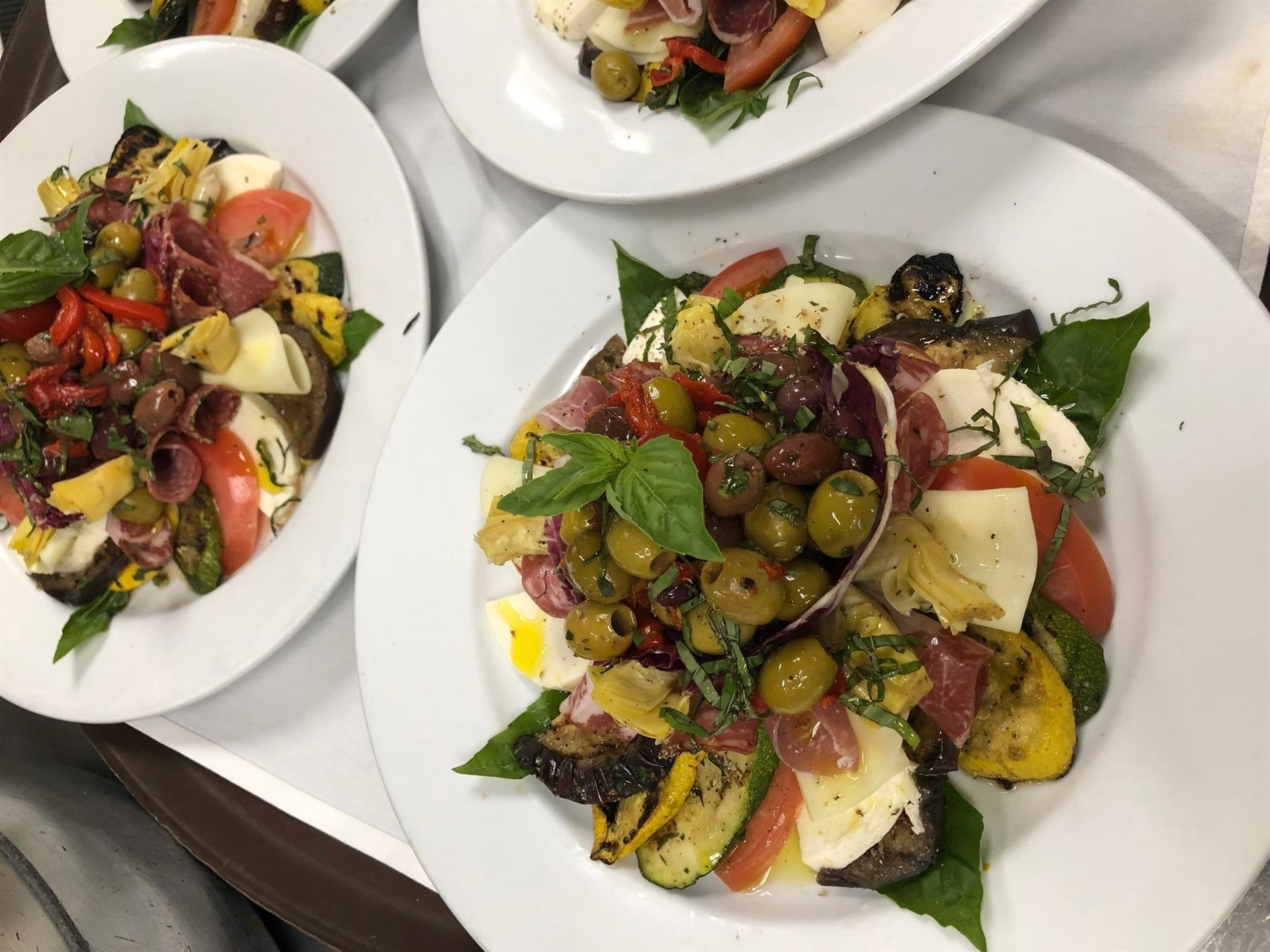 An assortment of Antipasto Salads on dishes in the kitchen