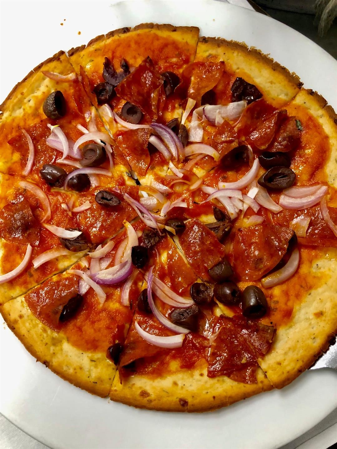 Pizza with sauce, olives, pepperoni, and chopped onion