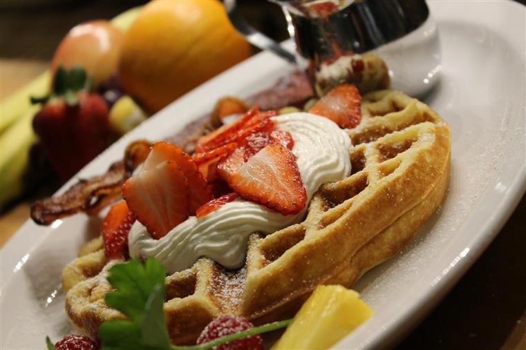 Belgian waffle topped with cream and strawberries