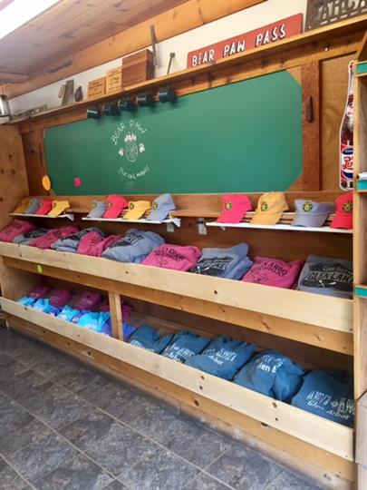 souvenir hats and shirts displayed in shelves