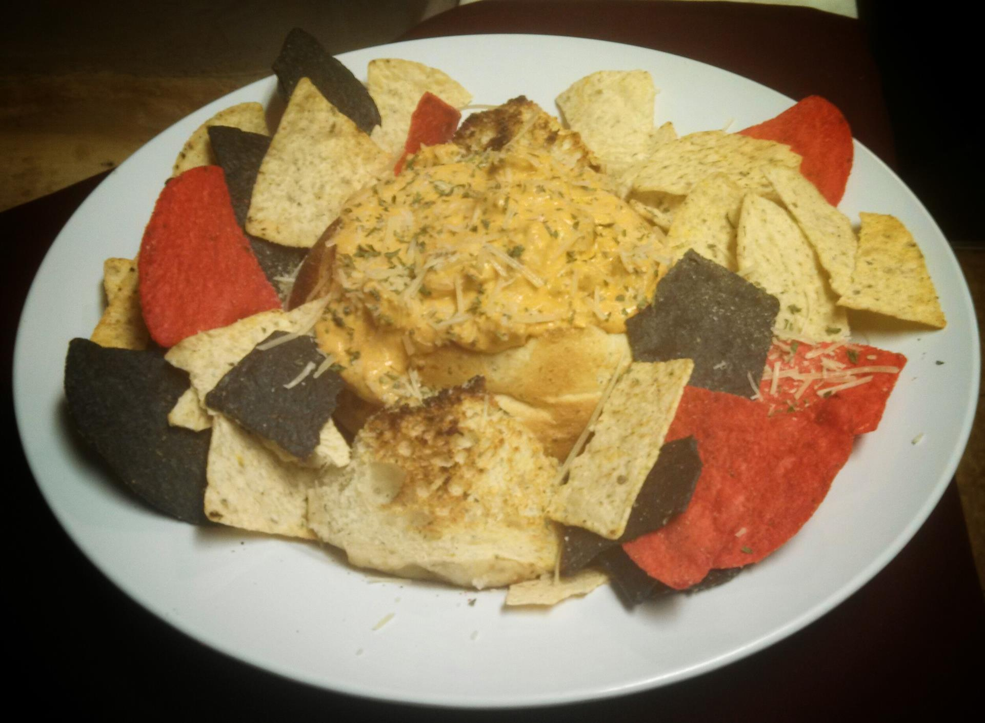 plate of tortilla chips with dip in the center of the plate