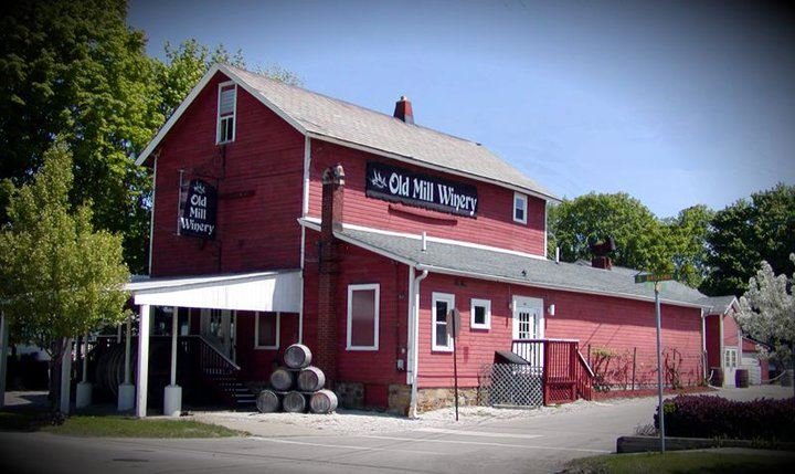 exterior of the old mill winery with wine barrels stacked together