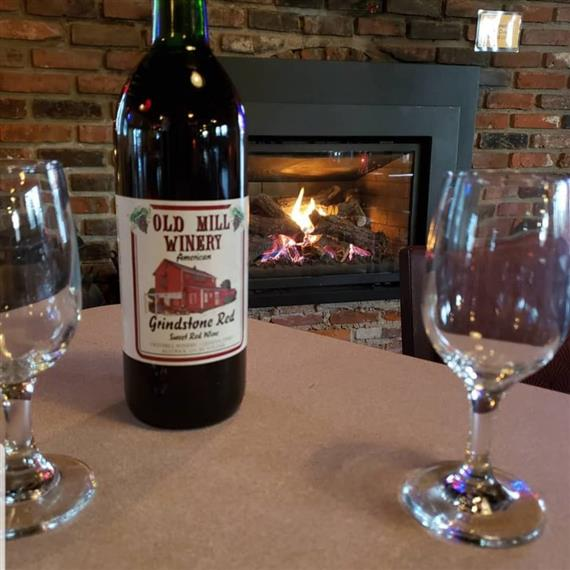 Bottle of Old Mill Winery Grindstone Red Wine on a table with two wine glasses in front of the burning fire.