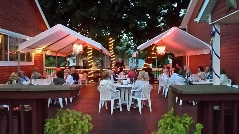 Outside patio area with tables and live band playing.