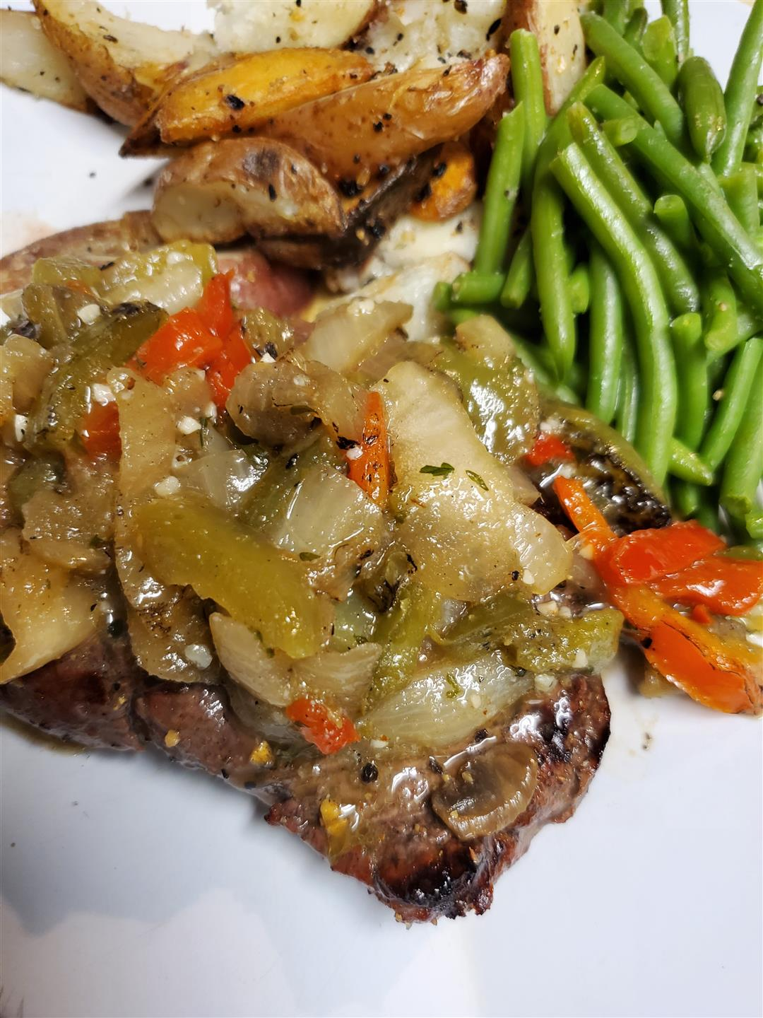 steak with peppers, onions, and side of green beas