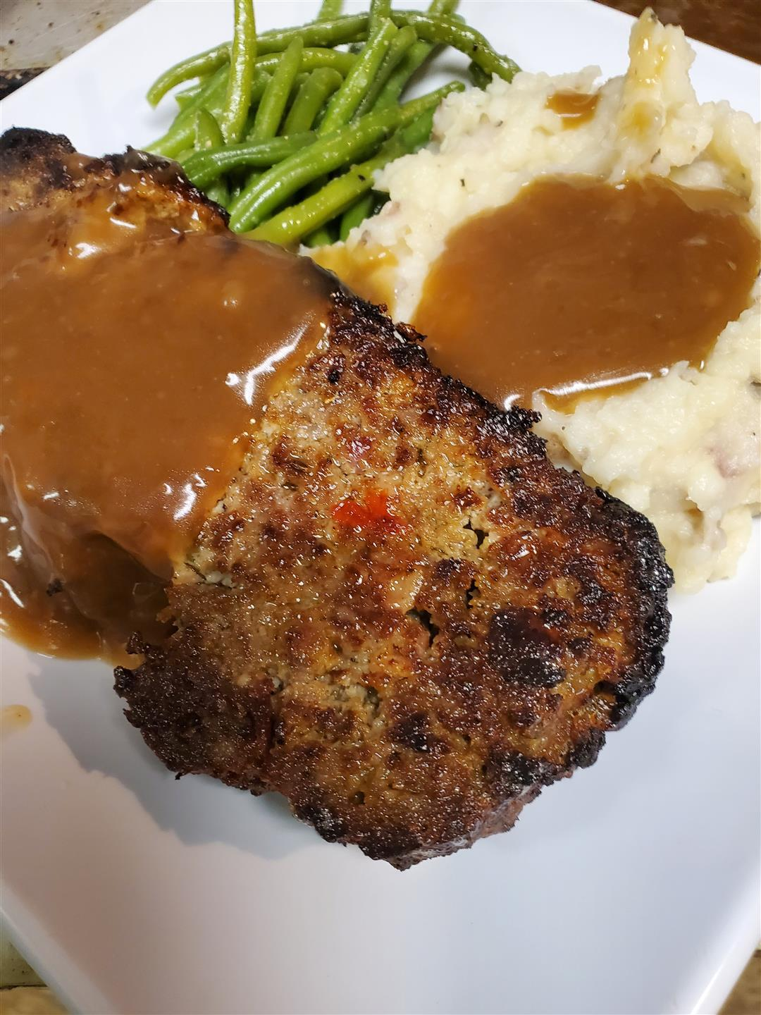 meat entree with mashed potatoes, gravy and green beans