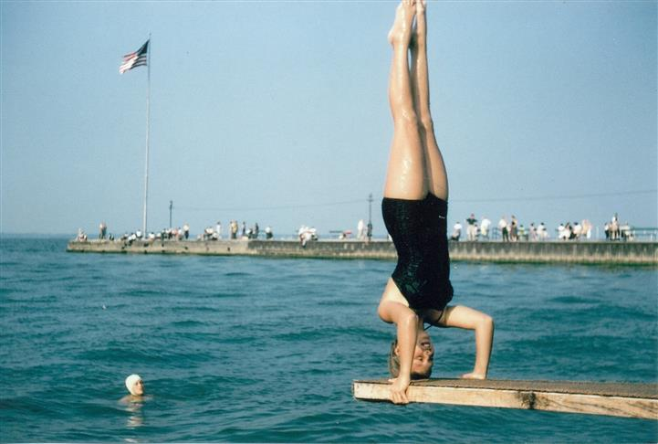 person doing headstand on diving board