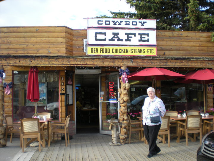 An old woman posing for photo outside Cowboy Cafe